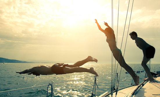 Young adults diving off a sailboat making memories on a cruise excursion